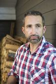 stock photo of firewood  - portrait of a man in a plaid shirt in front of firewood - JPG