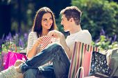 stock photo of nibbling  - A young loving couple resting on a park bench after shopping enjoying the sun while nibbling popcorn - JPG