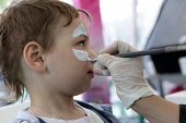 picture of face painting  - The serious child having his face painting - JPG
