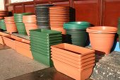 stock photo of flower pots  - plastic flower pots and holders outside a shop - JPG