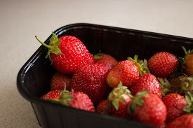 stock photo of sweet food  - Fresh strawberries in black supermarket plastic tray of packaging on the murble table - JPG