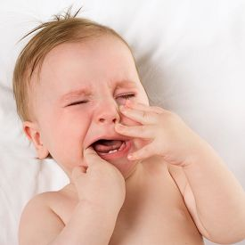 pic of teething baby  - baby lying on a white pillow and crying teething - JPG