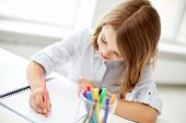 Постер, плакат: education creation art people and children concept happy girl drawing with felt tip pen in note
