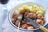 Coq au Vin, in old enamel bowl, with lacy napkin and vintage cutlery.  Traditional French chicken ca
