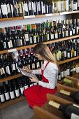 Постер, плакат: Saleswoman Taking Inventory In Wine Store