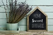 closeup of a house-shaped chalkboard with the text home sweet home written in it and a bunch of lave poster