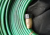 stock photo of tarp  - (Coiled hose) laying on tarp with creases - JPG
