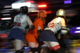 foto of roller-derby  - Three women on skates compete in a roller derby - JPG
