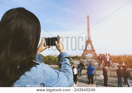 poster of Woman Tourist Taking Photo By Phone Near The Eiffel Tower In Paris Under Sunlight And Blue Sky. Famo