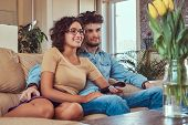 Happy Young Couple Cuddling While Watching Tv In Their Living Room. poster