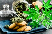 Cookies With Buds Cannabis And Of Marijuana On The Table. A Can Of Cannabis Buds Concept Of Cooking  poster