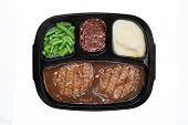 pic of frozen tv dinner  - An unhealthy Salisbury steak TV dinner with gravy mashed potatoes and a brownie dessert in a plastic tray isolated on white - JPG