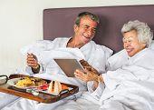 Couple having breakfast in bed poster
