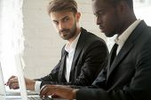 Suspicious Cunning Male Caucasian Worker Looking At Serious Working African American Colleague, Feel poster