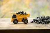 A Small Yellow Toy Truck Is Loaded With Sunflower Seeds Next To A Small Pile Of Sunflower Seeds. A C poster