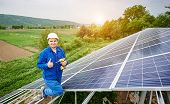 Construction Worker With Screwdriver Looking In Camera With Thumb-up Gesture On Photo Voltaic Panel  poster