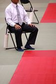 pic of shotokan  - The karate referee sitting beside the mat - JPG
