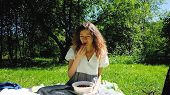 European Girl Eats Strawberries In The Nature. A Young Woman Sits On The Grass And Eats Berries On A poster