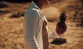 Faceless Man Holds Pineapple Fruit In Hand, Desert, Dry Ground On Background. Tropical Exotic Fruit  poster