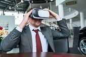 Bearded Customer Wearing Classical Suit Sitting At Wooden Table And Using Vr Headset While Undergoin poster