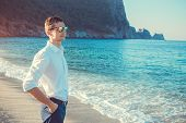 Young Businessman Looks At The View Of Mediterranean Sea Surrounded With Mountains. Guy Chilling And poster