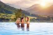 Kids Play In Outdoor Infinity Swimming Pool Of Luxury Spa Alpine Resort At Sunset In Alps Mountains. poster