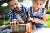 Father With A Small Daughter Outside With Hammer Making Wooden Birdhouse Or Bird Feeder. poster
