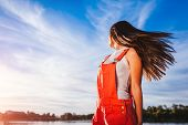 Happy And Free Young Woman On Blue Sky Background Enjoying Life. Girl Chilling On River At Sunset poster