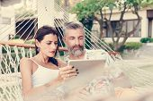 Couple using a tablet in a hammock poster