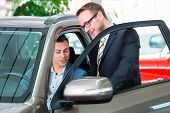 Customer buying new car in auto dealership and consulting salesman poster