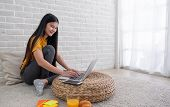 Asian Female Sit With Knees Up On Floor Using Laptop On Wicker Stand Near Window In Living Room At H poster
