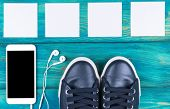 Overhead View Of Sports Shoes By Mobile Phone With Isolated Screen And In-ear Headphones And White E poster