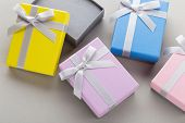 Small Colorful Jewelry Gift Boxes With Bows On Gray Background. Present Boxes For Jewelry Set poster