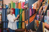 Mature Fabric Store Owner Standing In Her Shop Surrounded By Colorful Cloths And Textiles Taking Inv poster