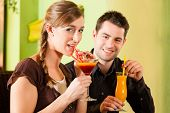Young happy couple drinking cocktails in bar or restaurant; presumably it is a first date