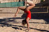A Young Girl In A Red Swimsuit Performs Acrobatic Elements On A Volleyball Court. Volleyball In The  poster