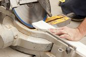 picture of baseboard  - Contractor Using Circular Saw Cutting New Baseboard for Renovation - JPG