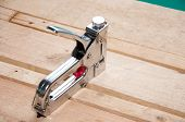 Tool For Assembling Furniture Close-up On A Wooden Background. Furniture Stapler poster