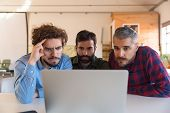 Group Of Male Entrepreneurs In Casual Staring At Laptop Monitor. Business Colleagues In Casual Meeti poster