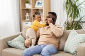 family, fatherhood and technology concept - happy african american father with baby at home calling  poster
