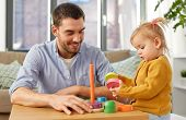 family, fatherhood and people concept - happy father and little baby daughter playing with pyramid t poster