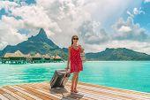 Hotel luxury resort tourist woman arriving with luggage suitcase in Tahiti Bora Bora honeymoon vacat poster