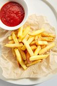 Fries or french fries on white restaurant plate with tomato sauce isolated. Sweet potato finger chip poster