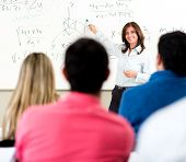 stock photo of classroom  - Teacher giving a lecture in a classroom and writing math formulas on the board - JPG