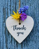 Thank You Or Thanks Greeting Card With Flowers And Decorative White Heart On Blue Wooden Background. poster