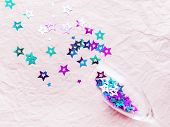 Transparent Wine Glass With Magenta And Cyan Colored Spangles. Festive Copy Space With Crockery On C poster
