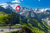 Swiss Flag Waving And Tourists Admire The Peak Of Jungfrau Mountain On Mannlichen Viewpoint, Bernese poster