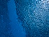 Aerial view of the sea surface with coral reef and bottom visible through the water, Shot in Hawaii, poster