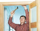 Male handyman carpenter at interior wood door installation with hammer