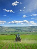 stock photo of plowing  - Farming tractor plowing and spraying on field vertical - JPG